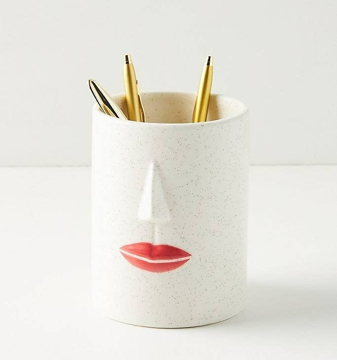 White cup with small black speckles and a nose and lips on the front with pens in it