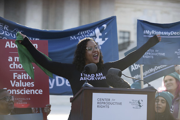 "Bracey Sherman stands at a podium with her arms in the air, wearing a shirt that reads ""I had an abortion"""