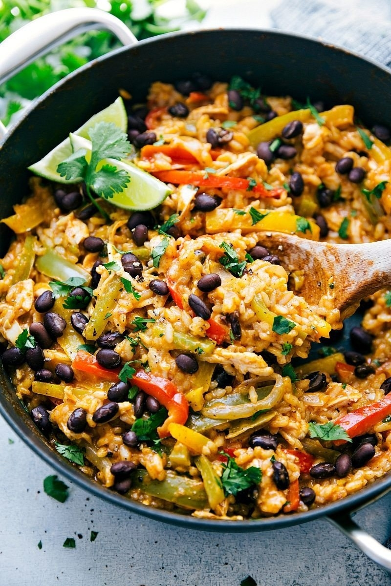 A skillet filled with cheesy rice, chicken, peppers, black beans, and herbs.