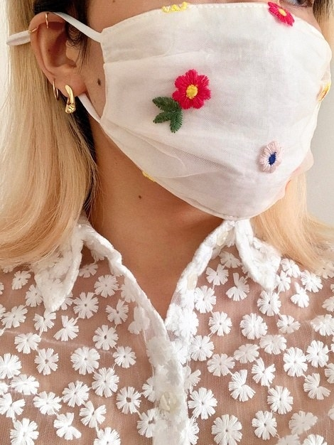 A model wearing a white face mask with embroidered floral details