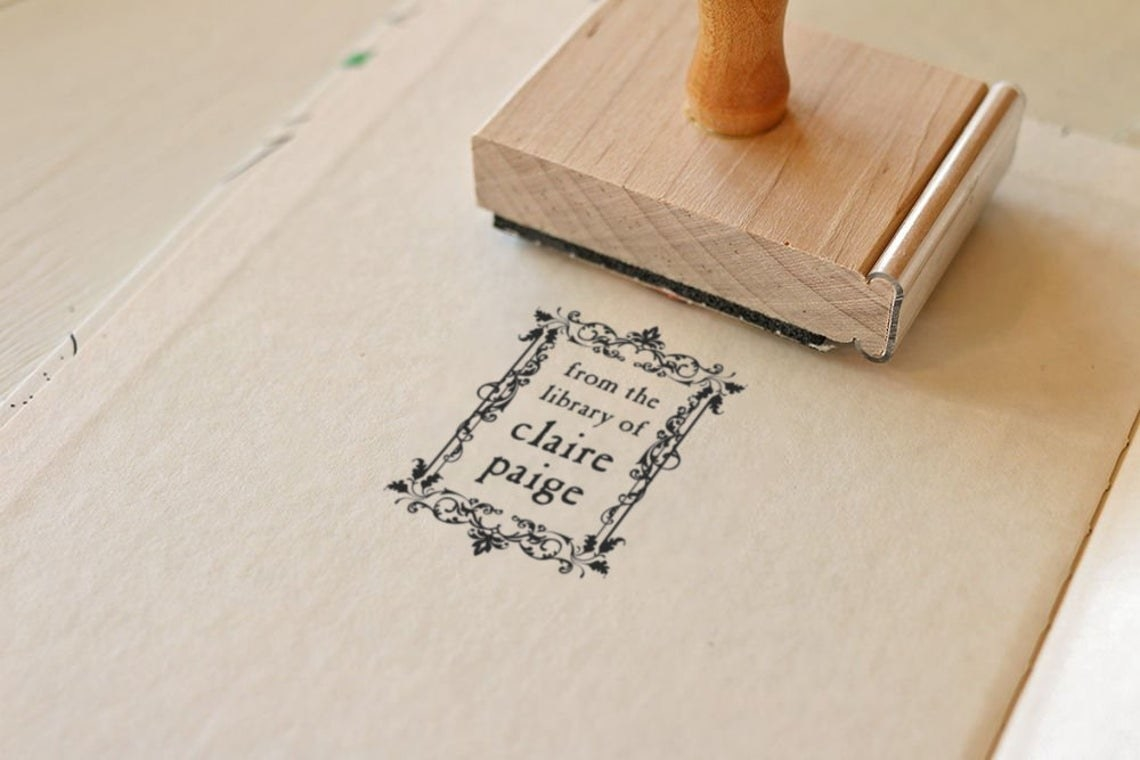"""A product shot of the wooden stamp having pressed a filigree-covered marking onto a book. It says """"from the library of claire paige."""""""