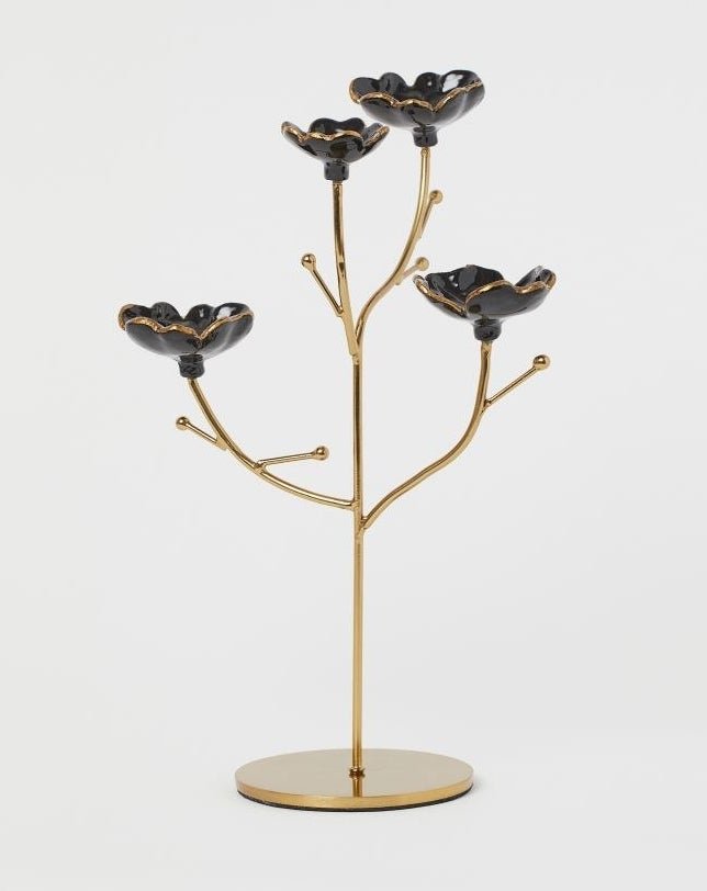 The gold jewelry holder with four stems with black and gold flower cups at the end