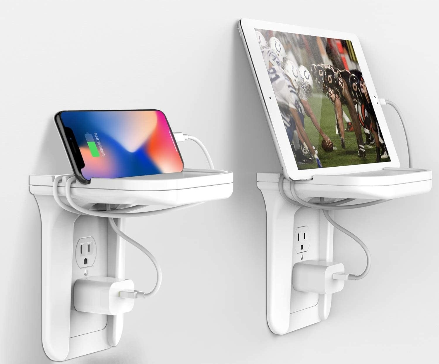 A phone and a tablet sitting on shelves above two electrical outlets.