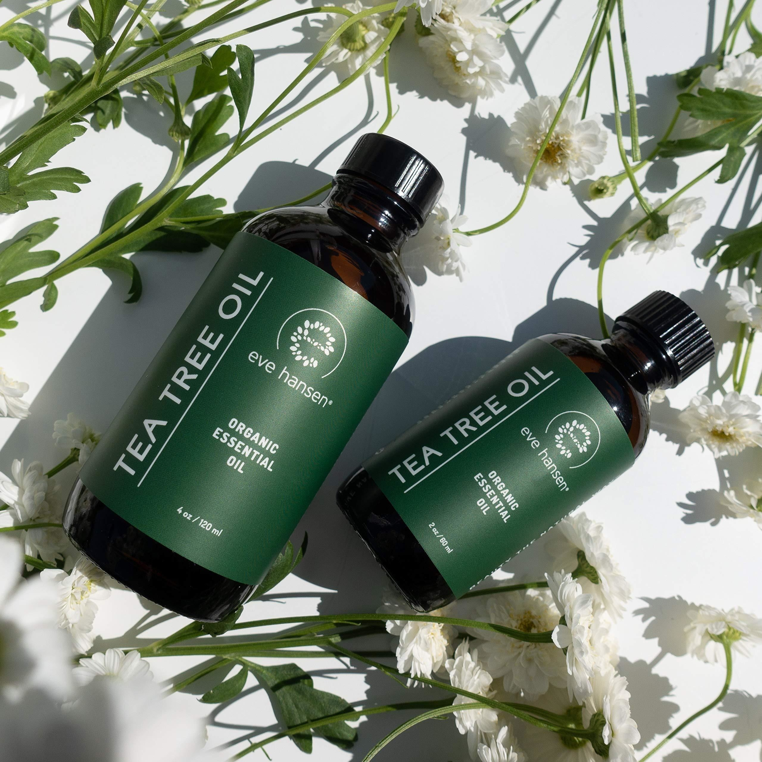 two different sizes of the tea tree oil with flowers in the background