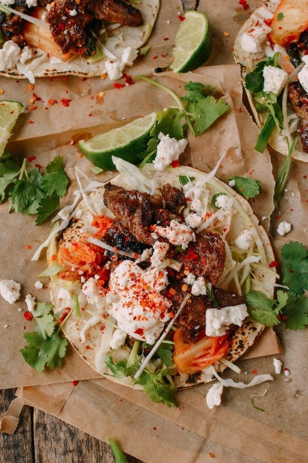 A taco topped with marinated beef bulgogi, kimchi, onion, cabbage, and queso fresco.
