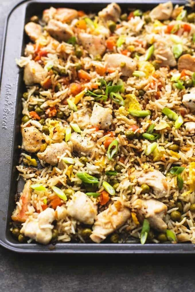 A sheet pan topped with rice, cubes of chicken, and vegetables like peas, scallions, and carrots.