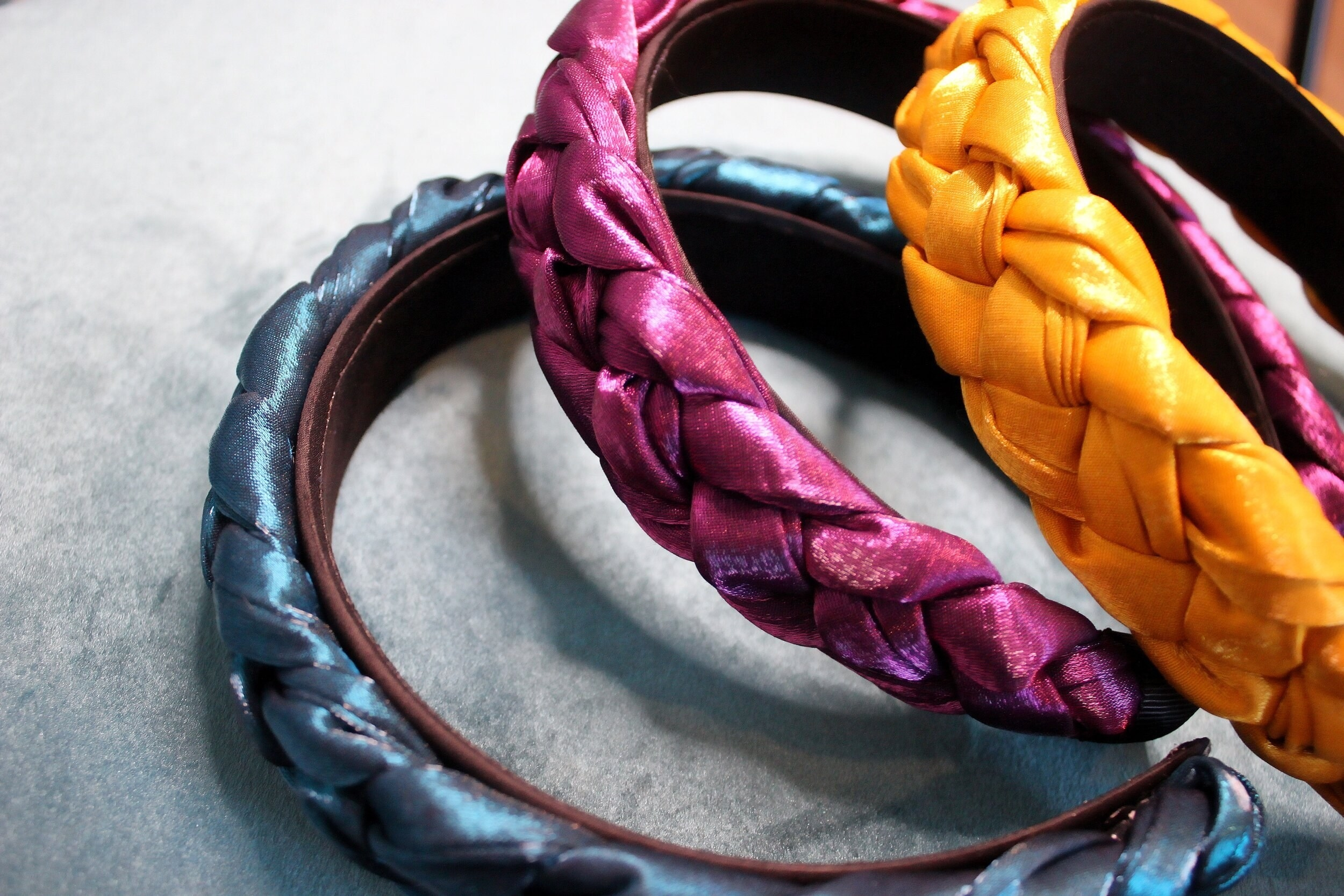 A blue, pink, and yellow braided headband sitting on top of each other