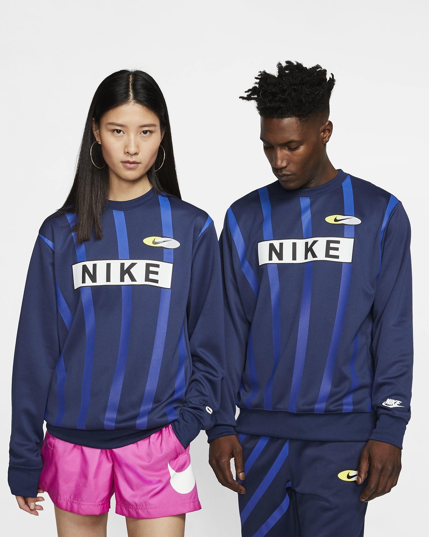 Two models wearing a navy sweatshirt with blue vertical stripes and large Nike logos