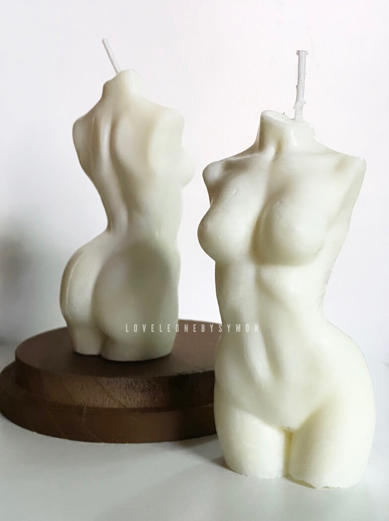 Two white wax candles that look like the female body