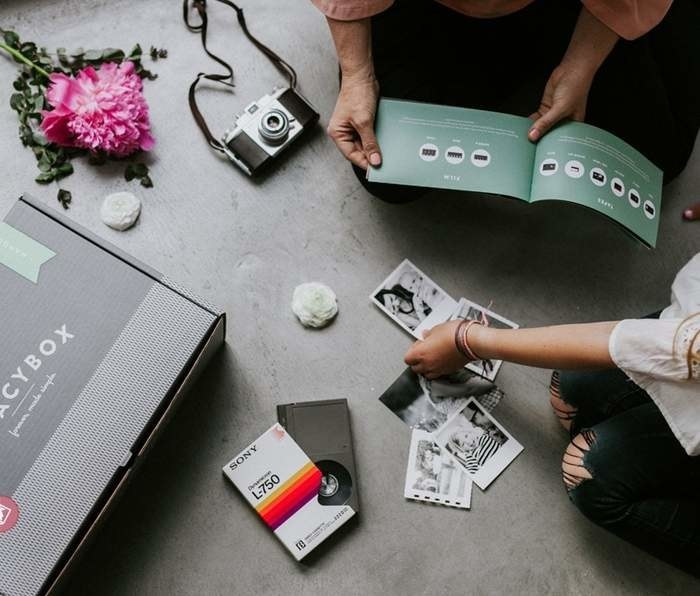 Models putting old photos and videotapes into a gray cardboard Legacy Box