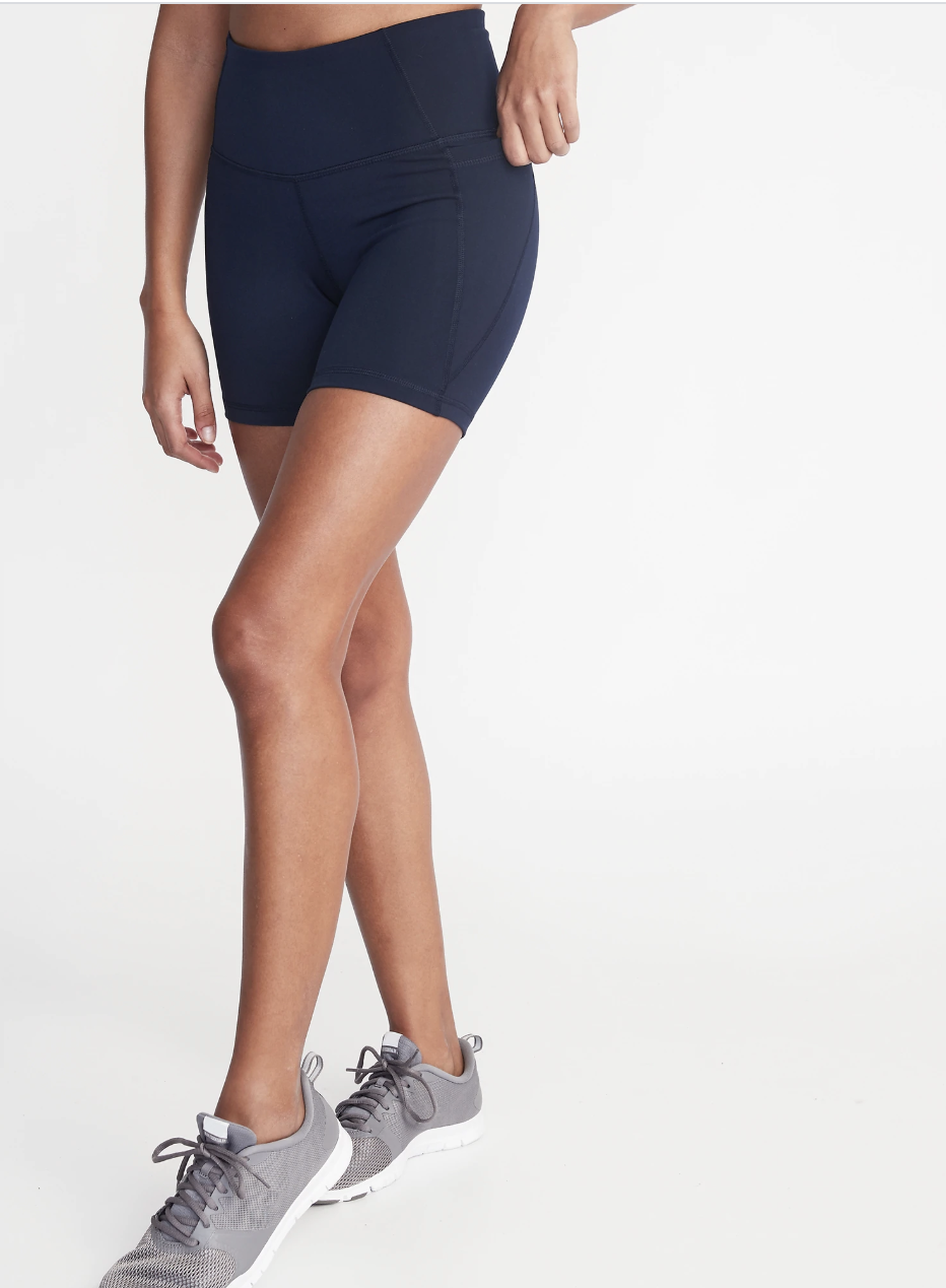 Model in navy blue mid-thigh length bike shorts