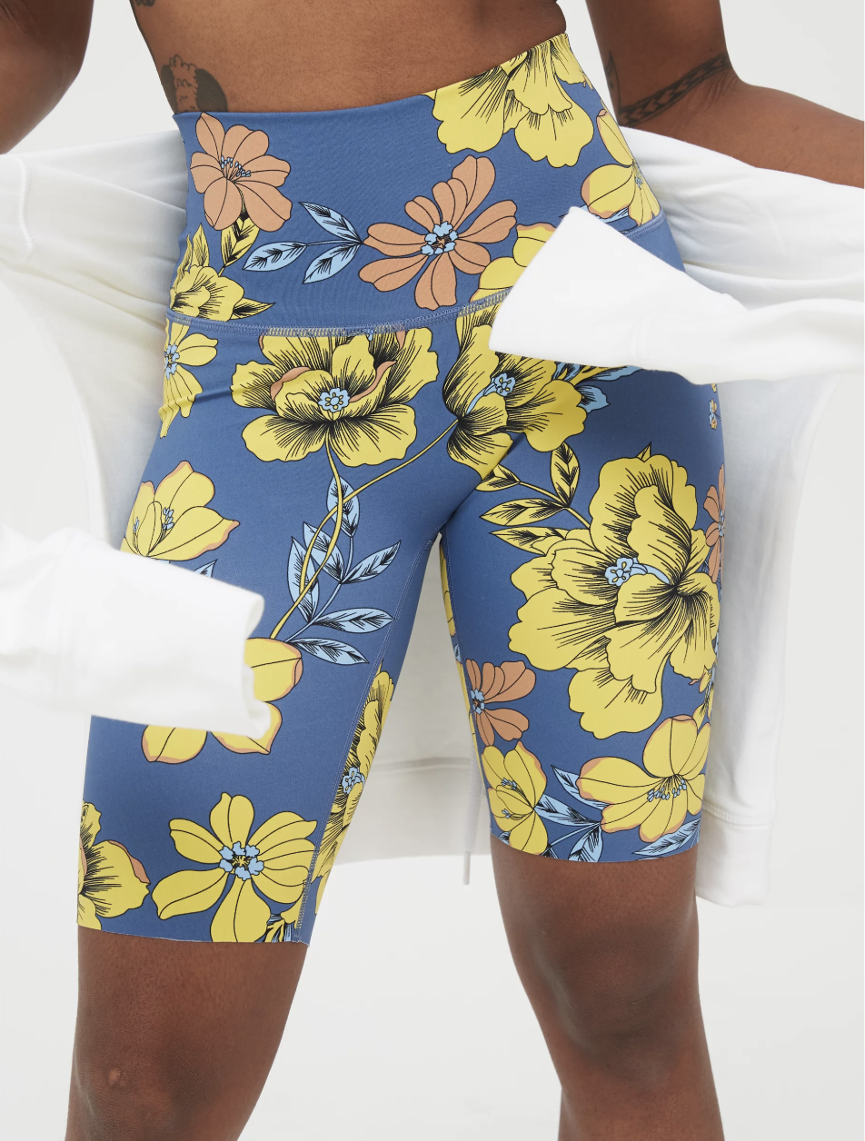 Model in blue bike shorts with yellow florals that cut off at the knee