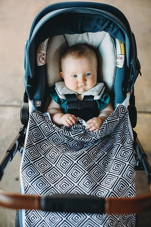 A black and white patterned blanket clipped over a baby in a stroller