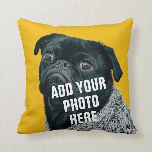 "A yellow pillow with a photo of a black pug and the words ""add your photo here"""