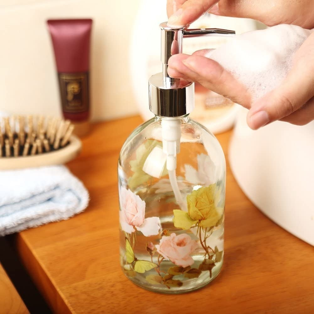 Clear glass soap dispenser with light pink and yellow flowers around the outside and a silver pump
