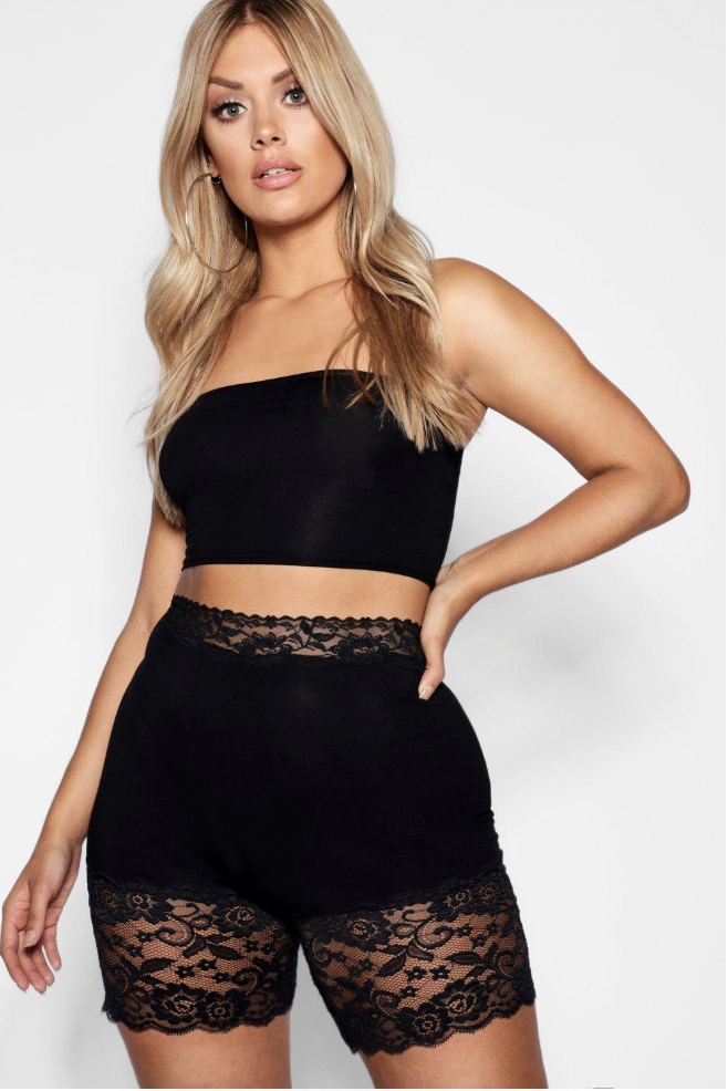 Model in black bike shorts with lace at the waist and legs