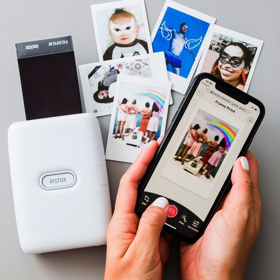 A person editing a photo on their phone and printing it with the Instax printer