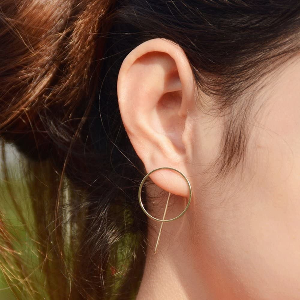 A gold circle on the front of the ear and a stick on the back