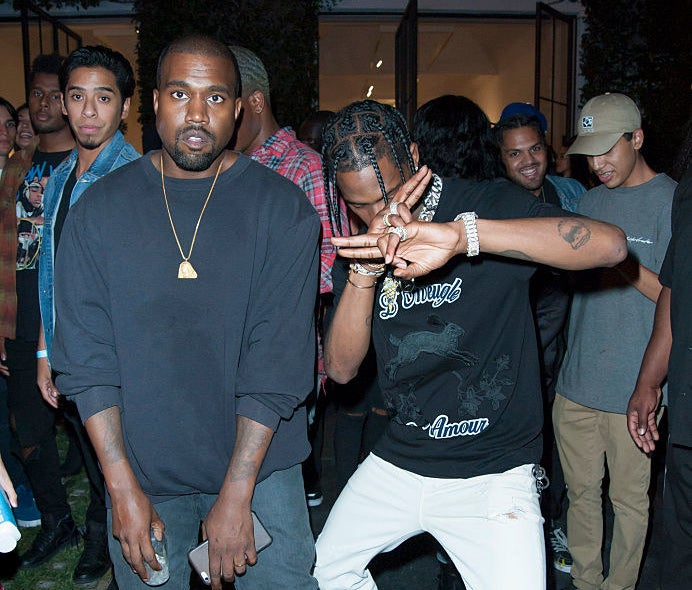 Kanye West and Travis Scott pose at an industry event