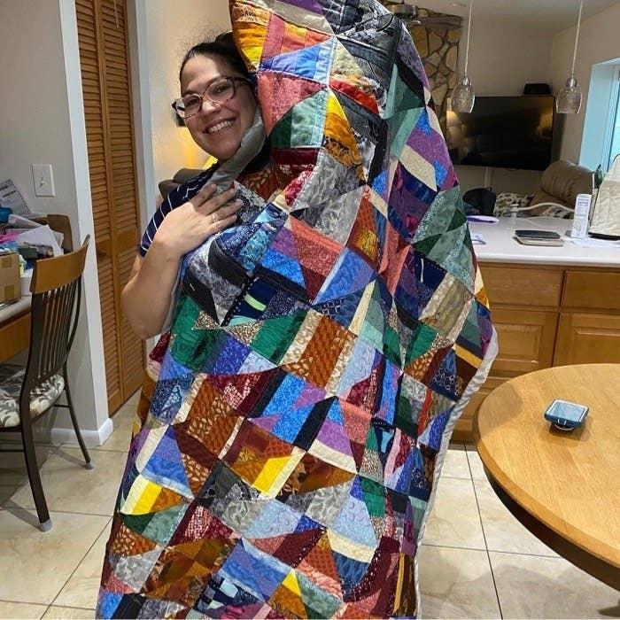 A woman proudly holding up a patchwork quilt that's bigger than she is