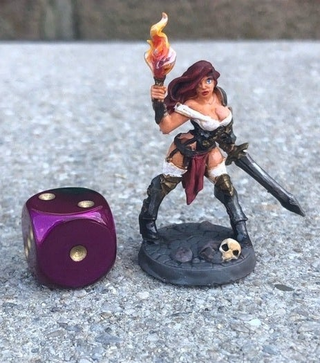 A figurine of a woman brandishing a sword and holding a torch next to a die