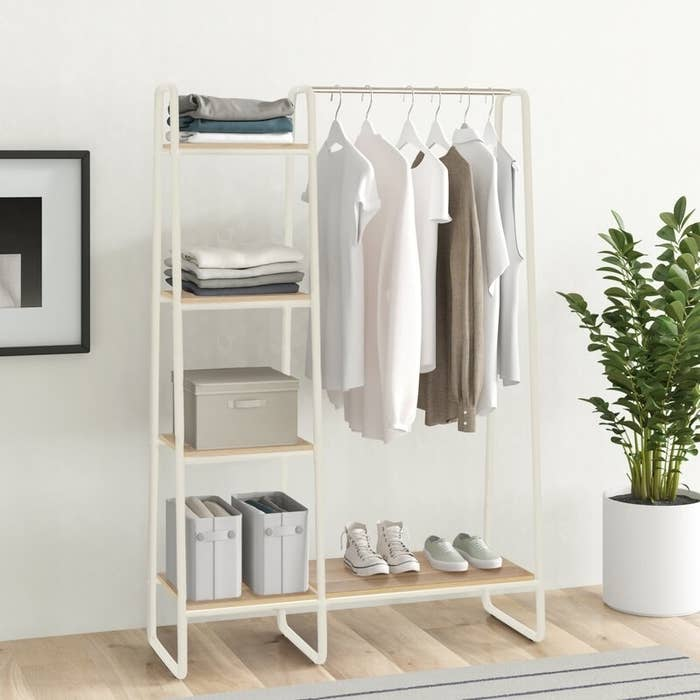 A white multi-shelf garment rack with a clothes bar