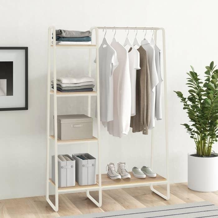A white multi-shelf garment rack with a clothes bar