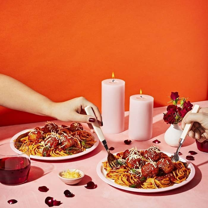 Two plates of spaghetti on a table with two hands twirling the noodles off one plate
