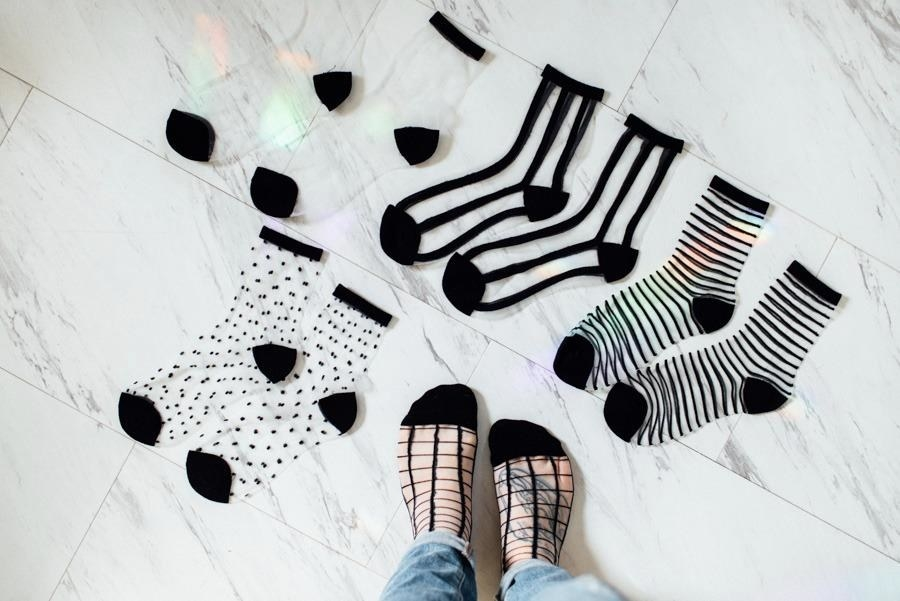 Reviewer pic of four pairs of clear mesh socks laid out on the ground with black toes, heels, and edge with assorted patterns in black, including polka dots, vertical, and horizontal stripes and one pair with checks on the reviewer's feet