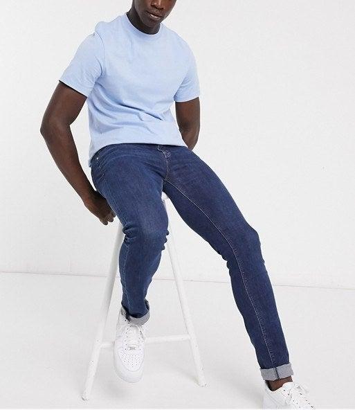 Model wearing fat dark blue skinny jeans