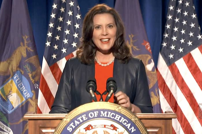 """Governor Gretchen Whitmer stands behind a lectern with a """"state of Michigan"""" seal on it"""