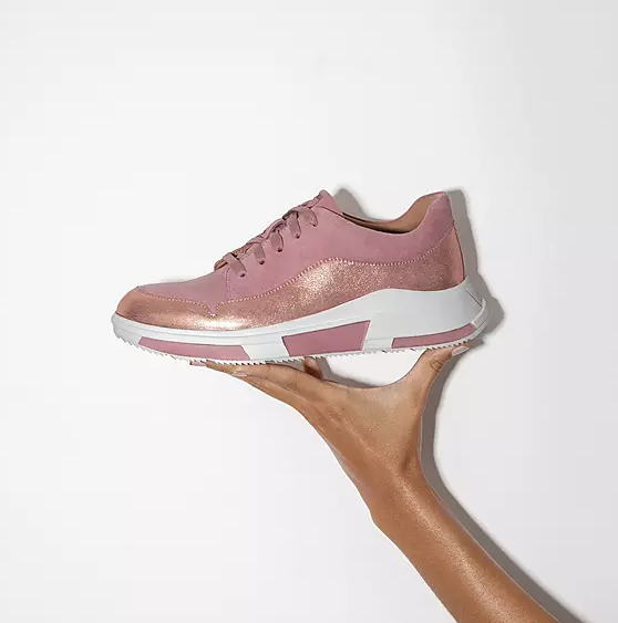 A person holding the pink suede sneaker