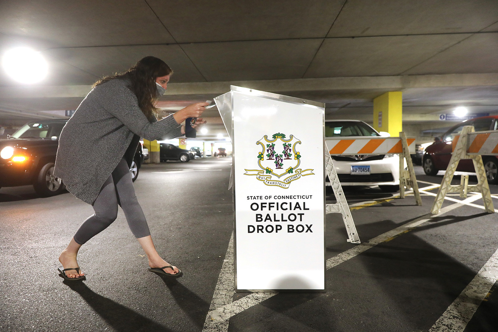A voter drops off a ballot in a ballot drop box in a parking garage