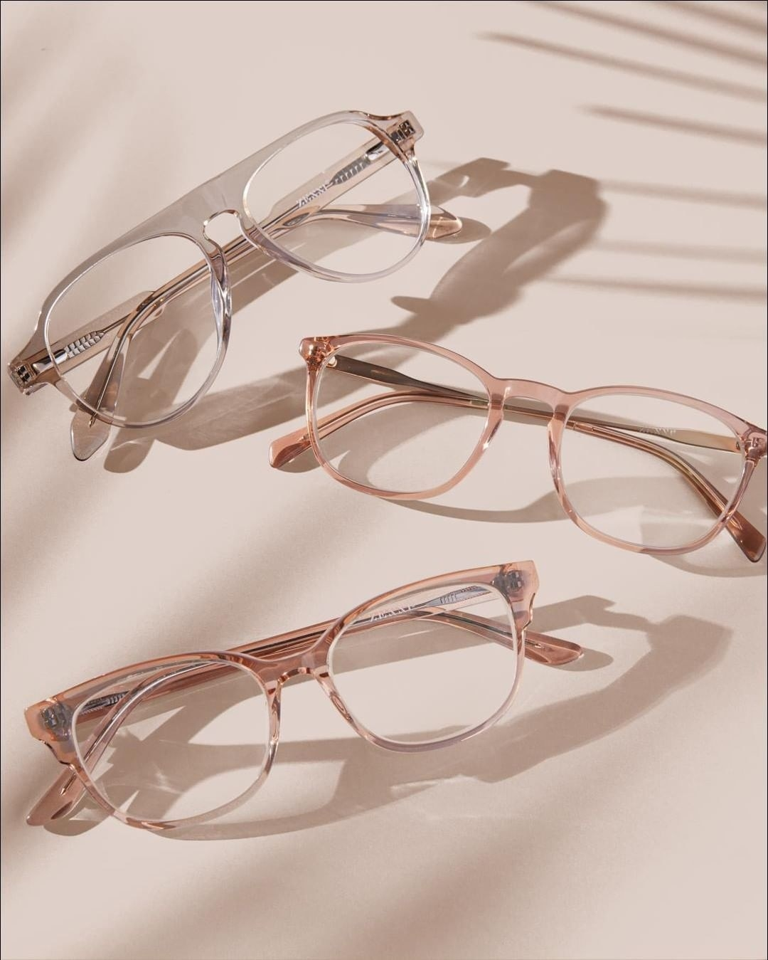 Three pairs of Zenni eyeglasses in a clearish, pink frame and different styles