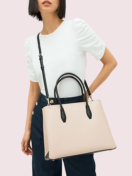 A model with a beige satchel with black straps hanging from their shoulder
