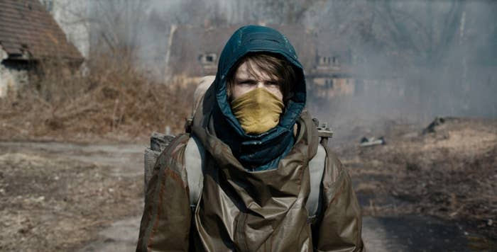 Dark still: Jonas wears a mask and walks through a post-apocalyptic town