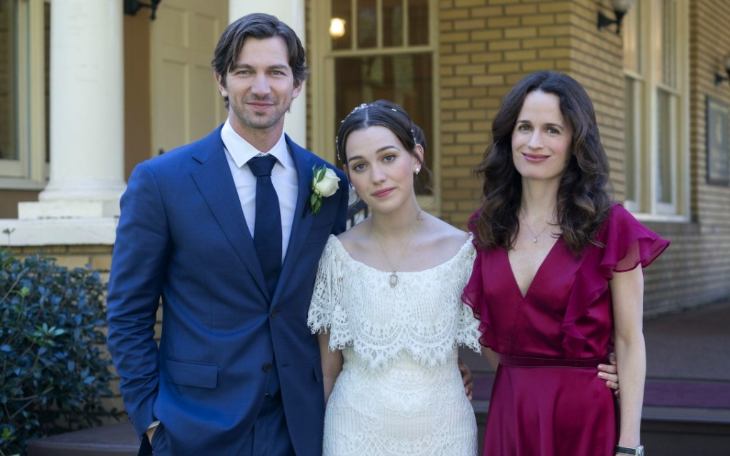 The Haunting of Hill House still: Eleanor stands in a wedding dress flanked by Steven in a suit and Shirley in a formal dress