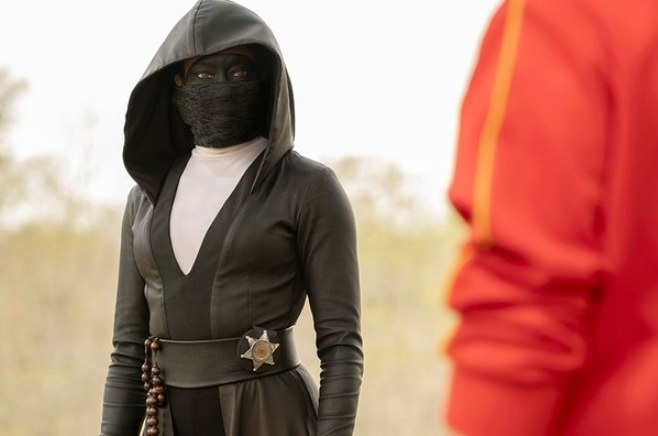 Watchmen still: Angela stands wearing a mask and black hooded outfit, facing someone not seen on camera
