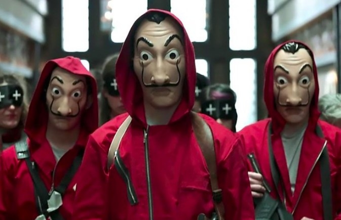 Money Heist still: Three men stand in masks and red hooded suits, with women wearing eye masks in the background
