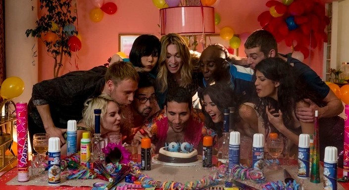 Sense8 still: The Sense8 cast lean over to blow out candles on a cake in a room decorated for a birthday party