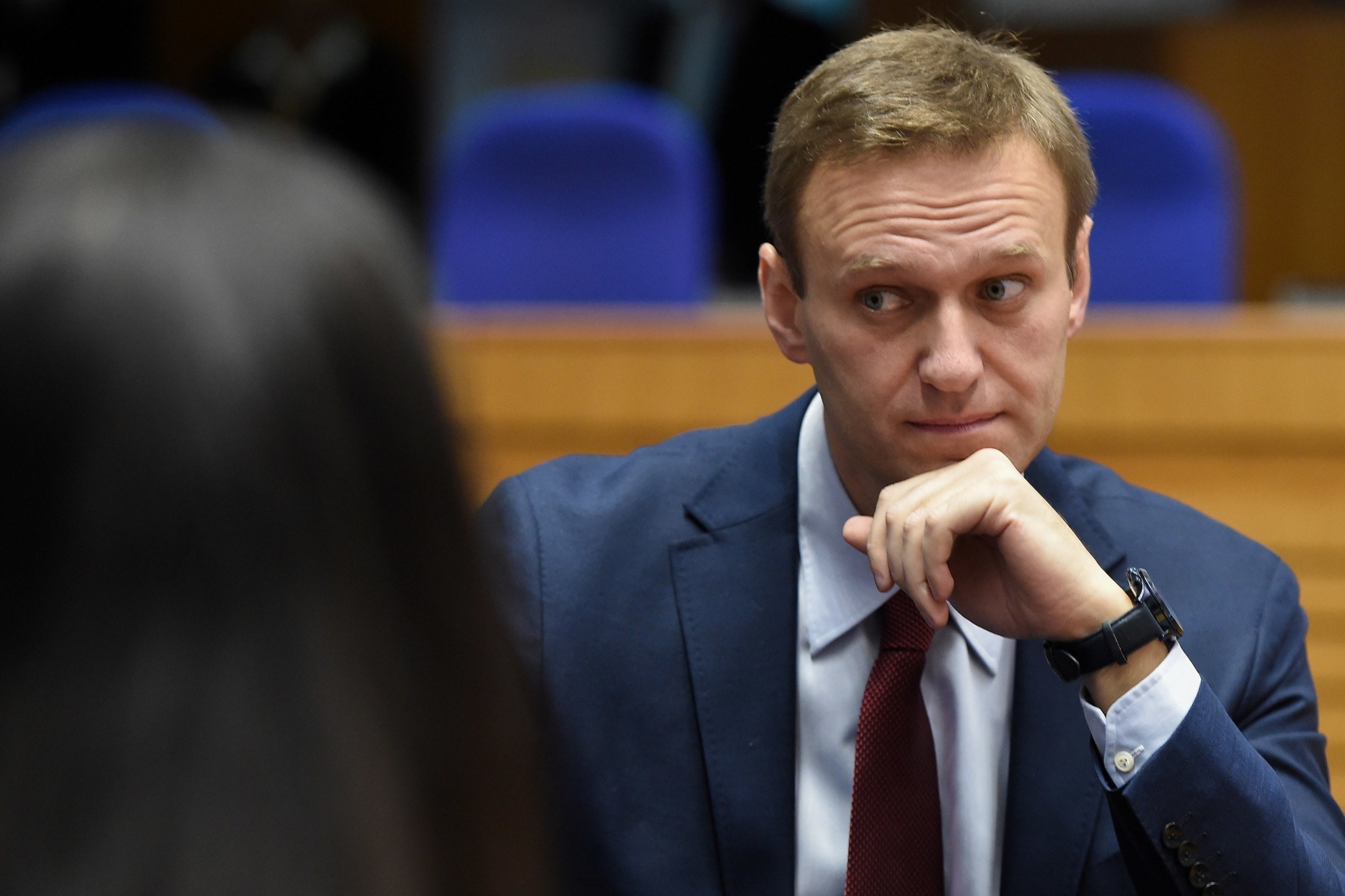 Navalny sits wearing a suit at a hearing