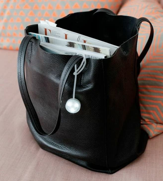 A purse light attached to the handle of a tote bag