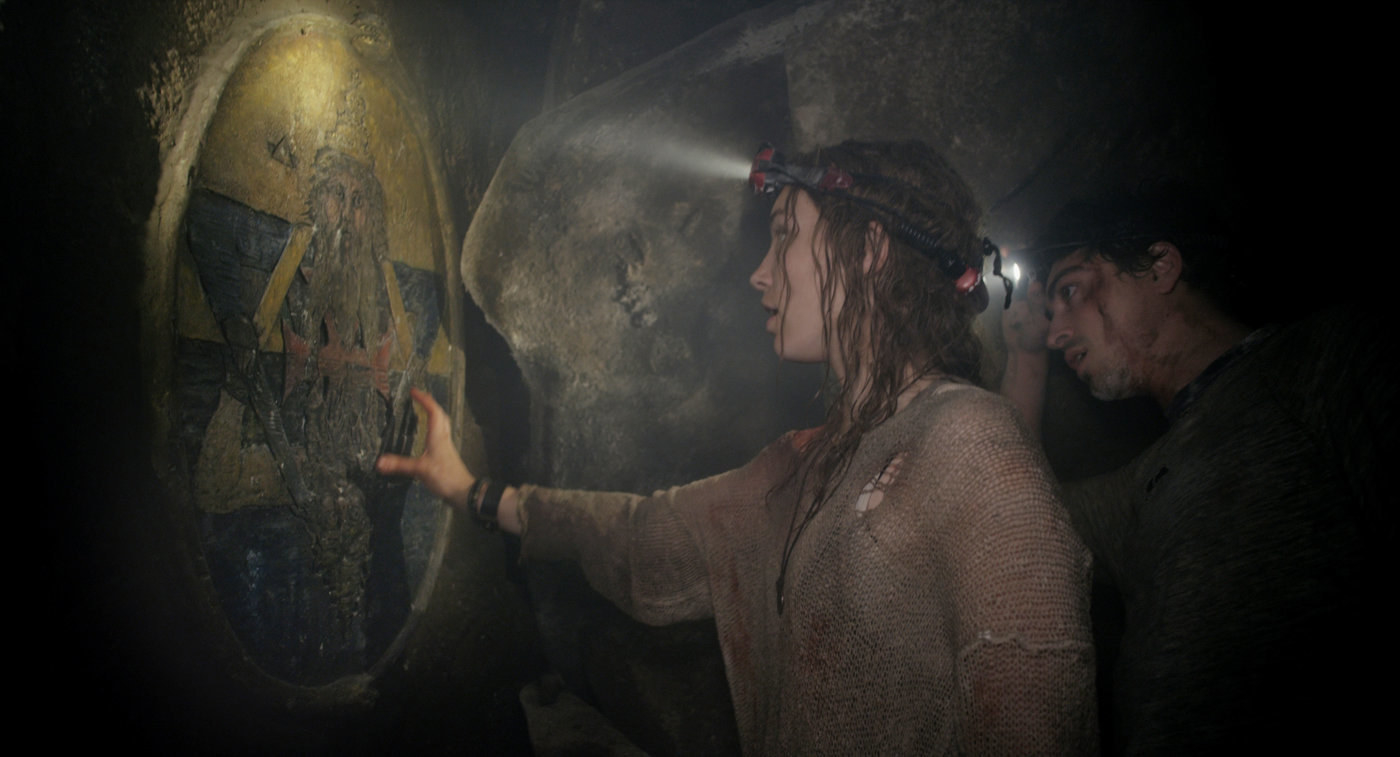 A woman and man are looking at an ancient-looking plaque somewhere underground, the woman reaches towards it
