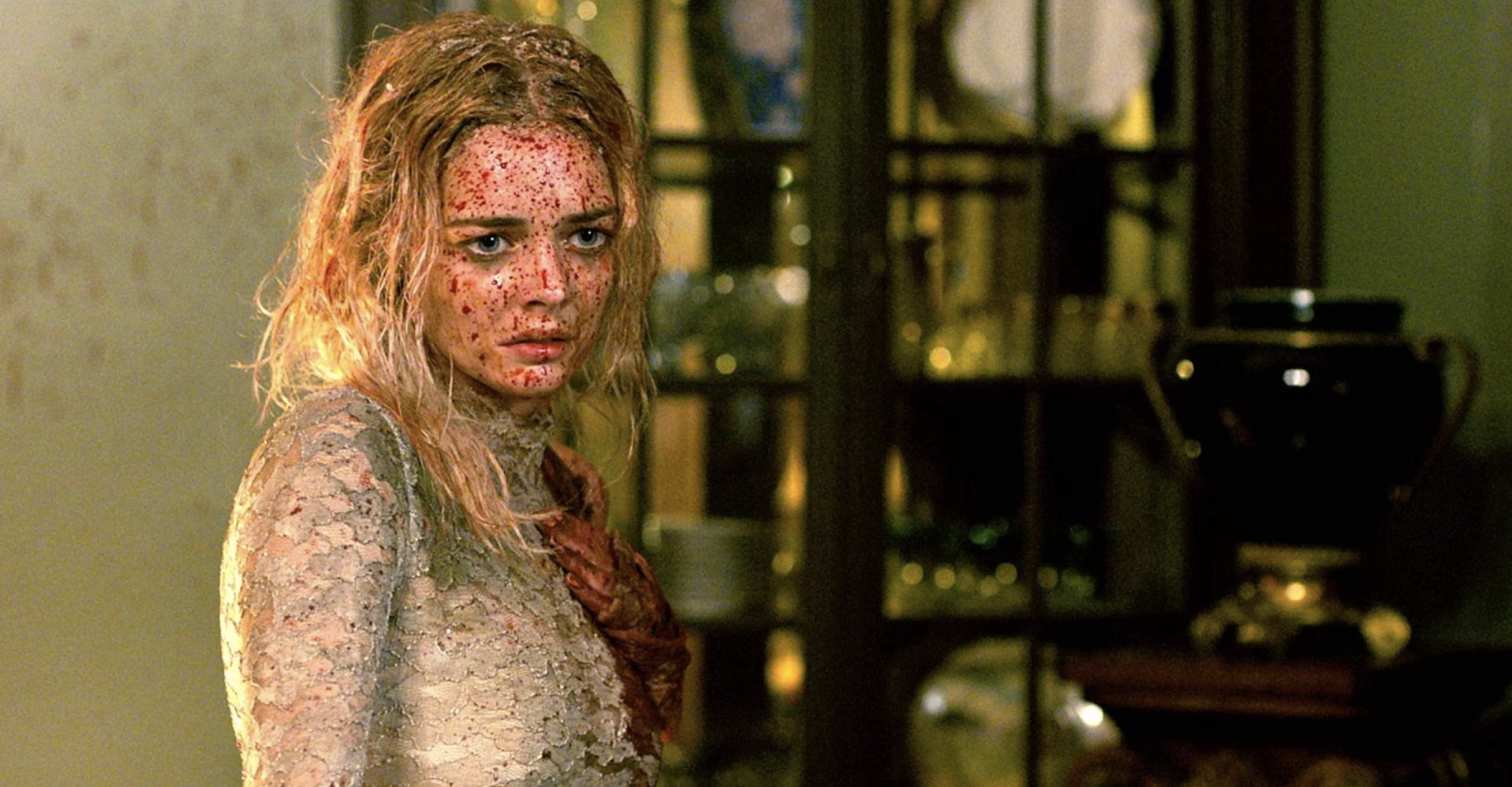 A woman wearing a wedding dress is spattered with blood, she holds her hand over her heart and looks sad