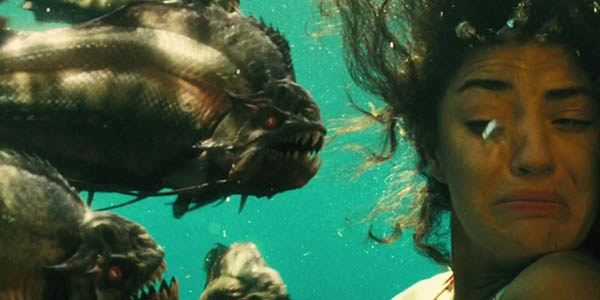 A woman is underwater with at least three huge piranhas right in front of her face, she turns away from them in fear