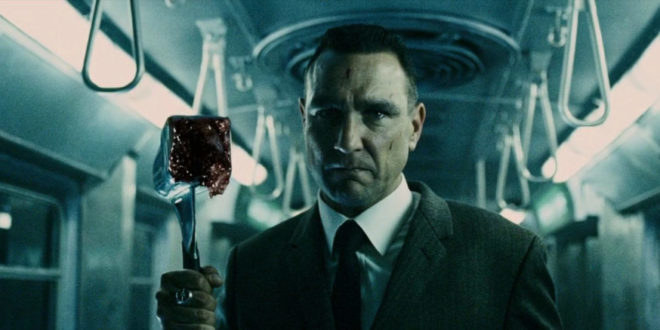 A man stands in a lit-up train carriage holding a bloody meat hammer