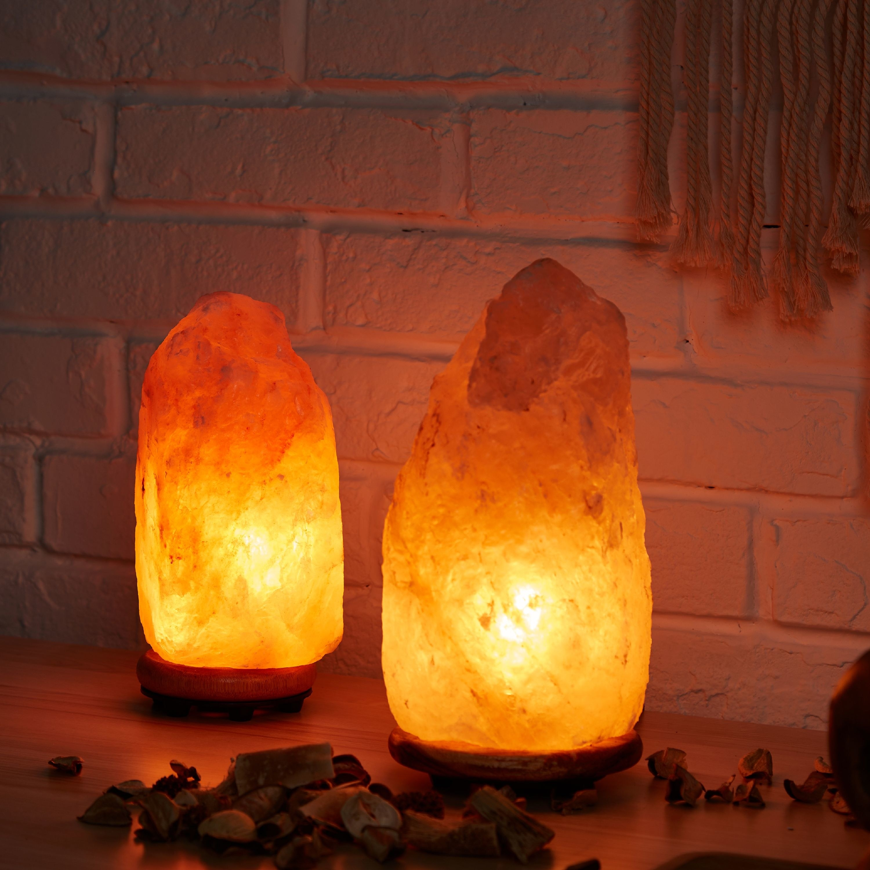 two Himalayan pink salt lamps lit in a dark room