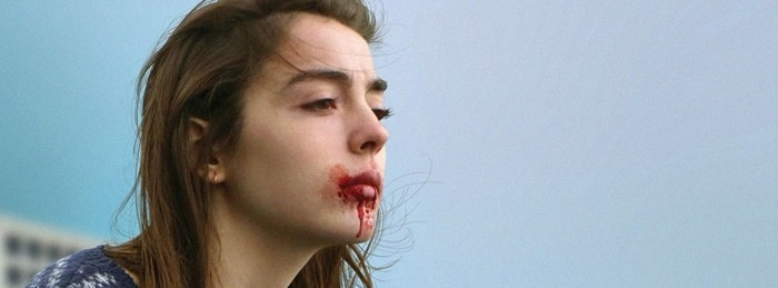 A girl looks into the distance with blood around her mouth
