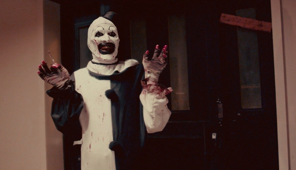 A creepy clown smiles while holding his hands up, in his hand is a small sharp tool