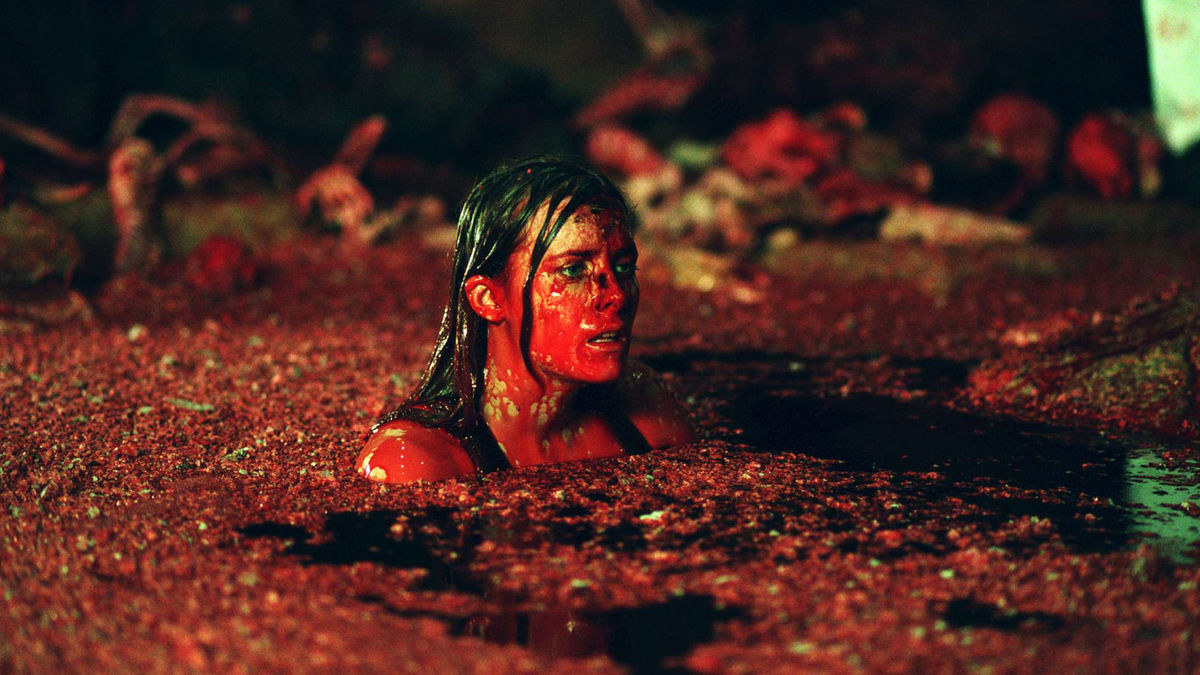 A woman stands in a pool of blood looking traumatised